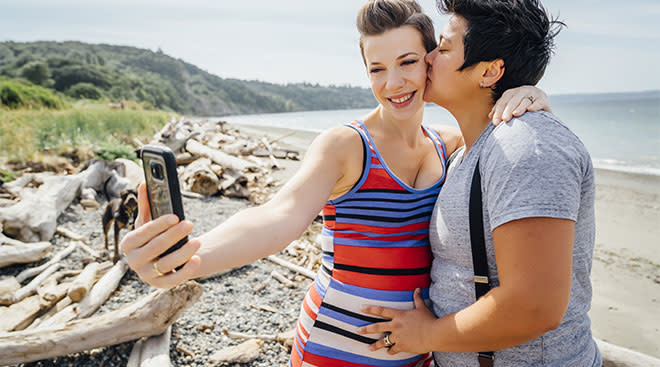 expecting couple taking selfie on the beach together