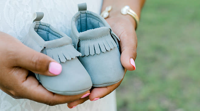 Close-up of pregnant woman holding baby moccasin shoes by her belly.