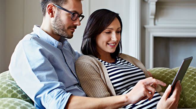 pregnant woman and her partner looking at tablet screen