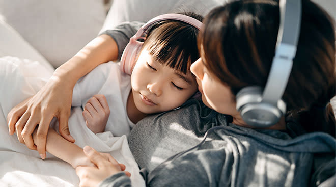 Young girl and her mom listen to podcast on headphones while laying in bed.