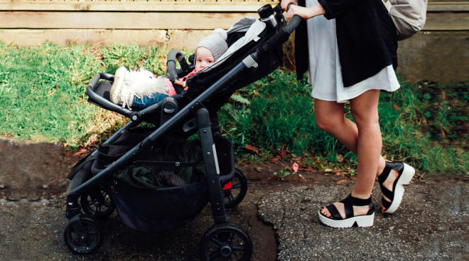 Mom pushing her baby in stroller outside.