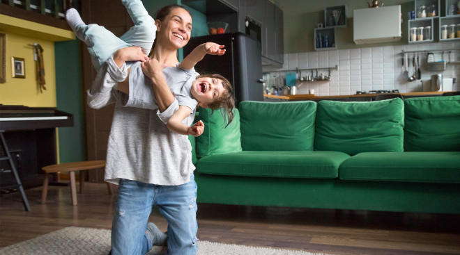 caregiver lifting up and playing with toddler