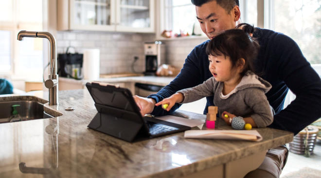 dad working from home with toddler daughter in his lap