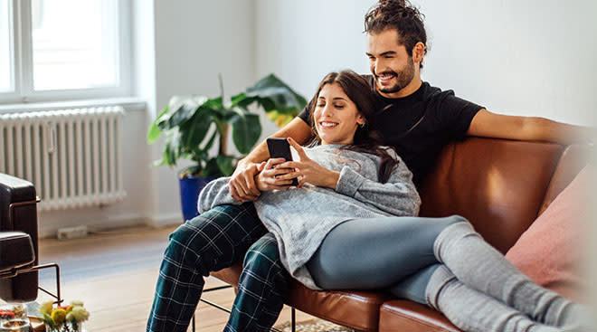 couple on the couch looking at phone screen