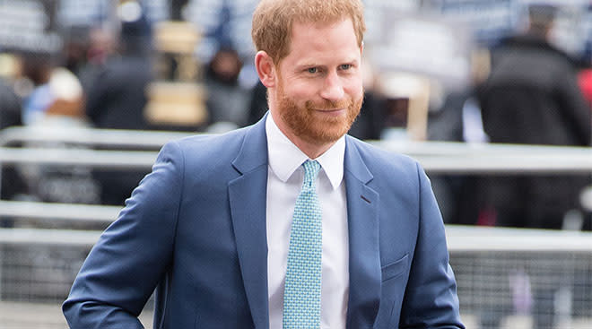 Prince Harry smiling and walking in a suit.