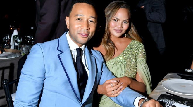 chrissy teigen and john legend sitting together at en event