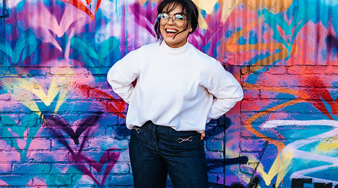 laughing woman in front of bright graffiti wall