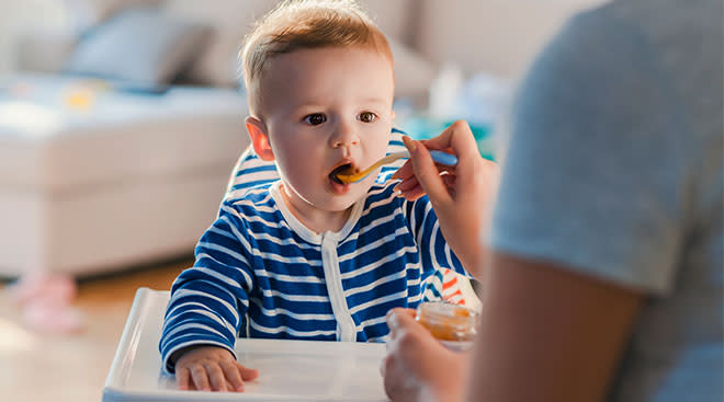 Parent feeding baby spoonful of baby food while baby his its mouth open.