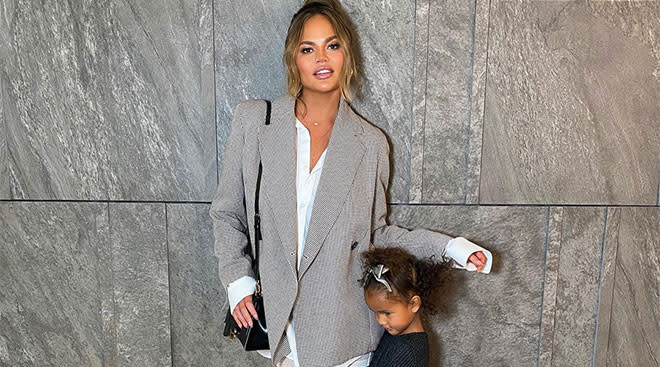 personality chrissy teigen pictured with her daughter hugging her legs