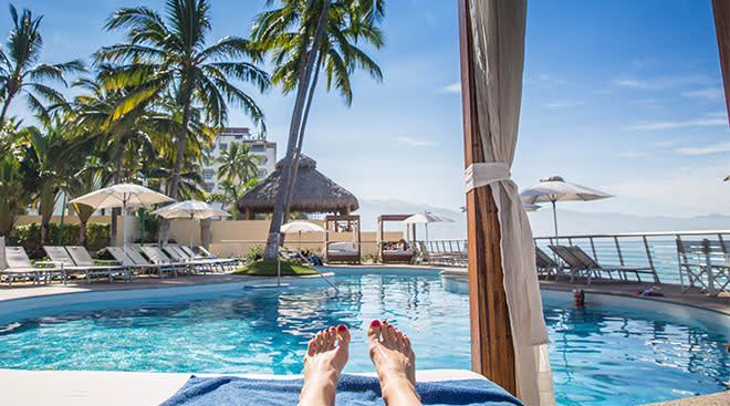 View of beach resort pool and woman's feet relaxing in her cabana.