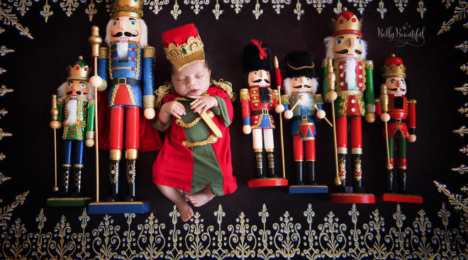 newborn baby dressed as the nutcracker prince, surrounded by actual wooden nutcrackers
