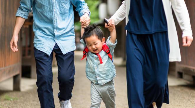 parent walking toddler boy to daycare