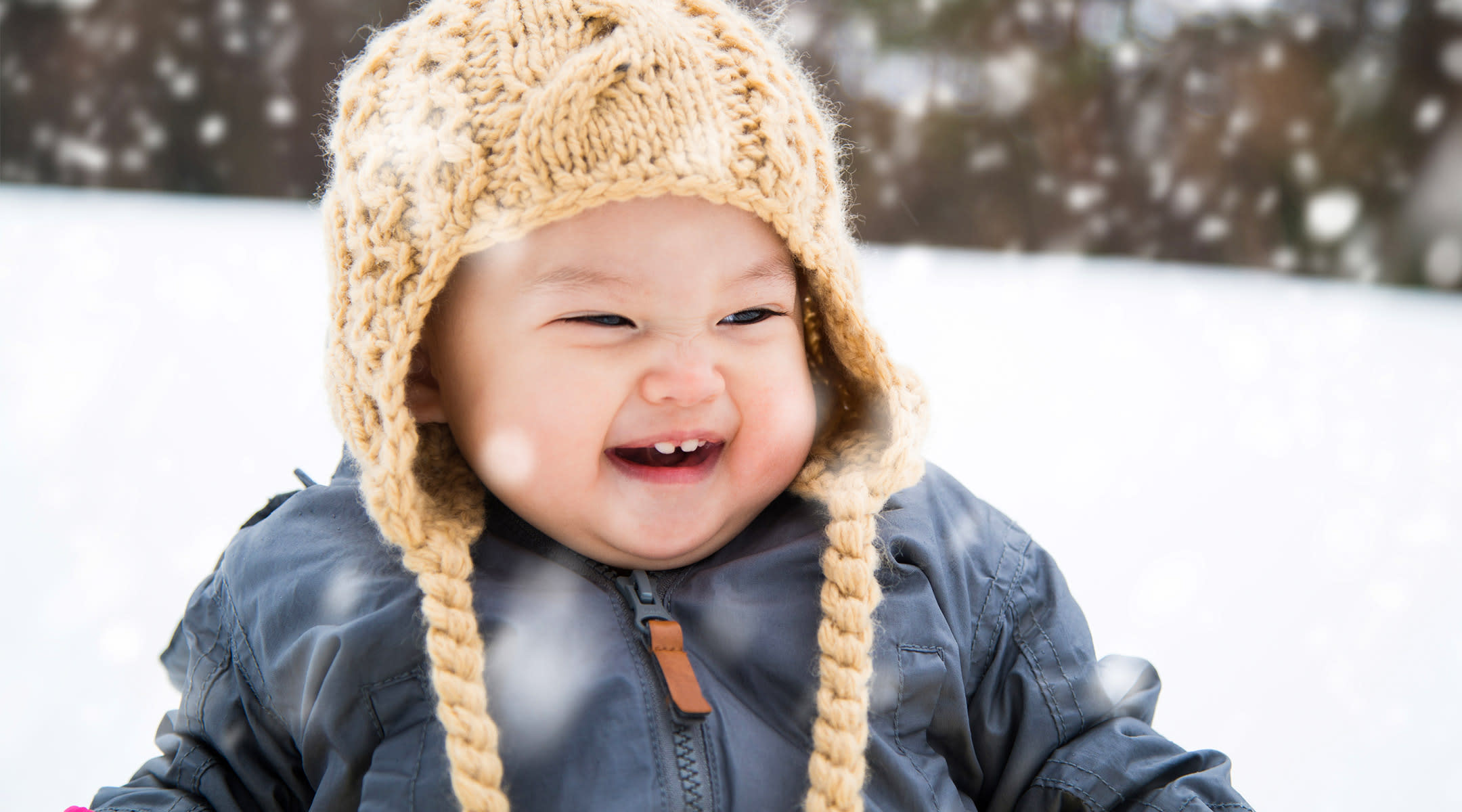 happy toddler wearing hat in the snow