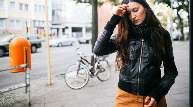 woman walking in urban environment and touching her forehead