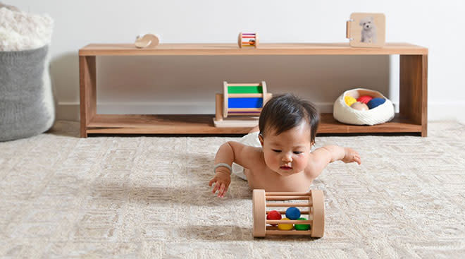 baby plays with wooden toy from his montessori style shelf