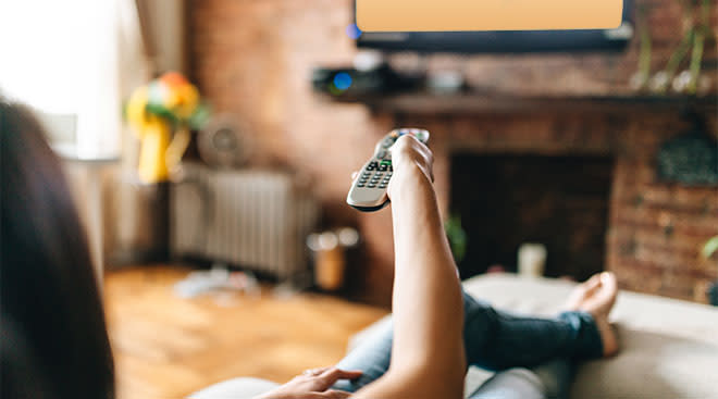 woman watching tv with remote in hand