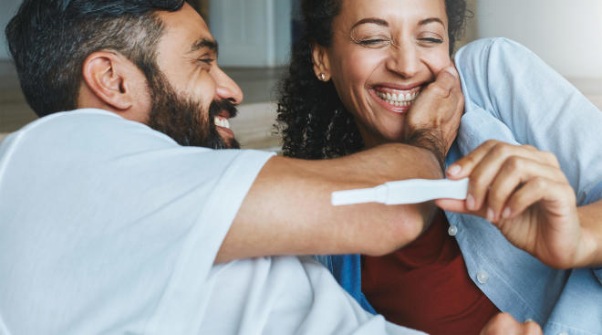 happy couple looking at positive pregnancy test