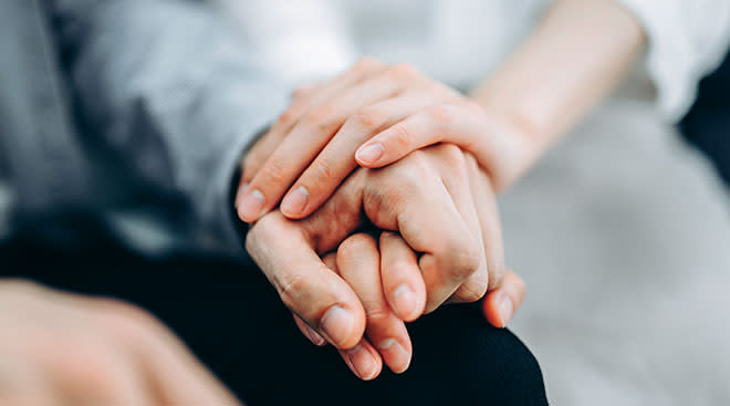 Close-up of couple comforting each other by holding hands.