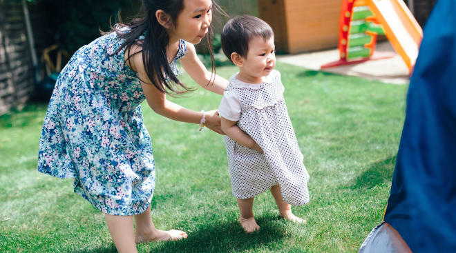 siblings playing outside in a backyard