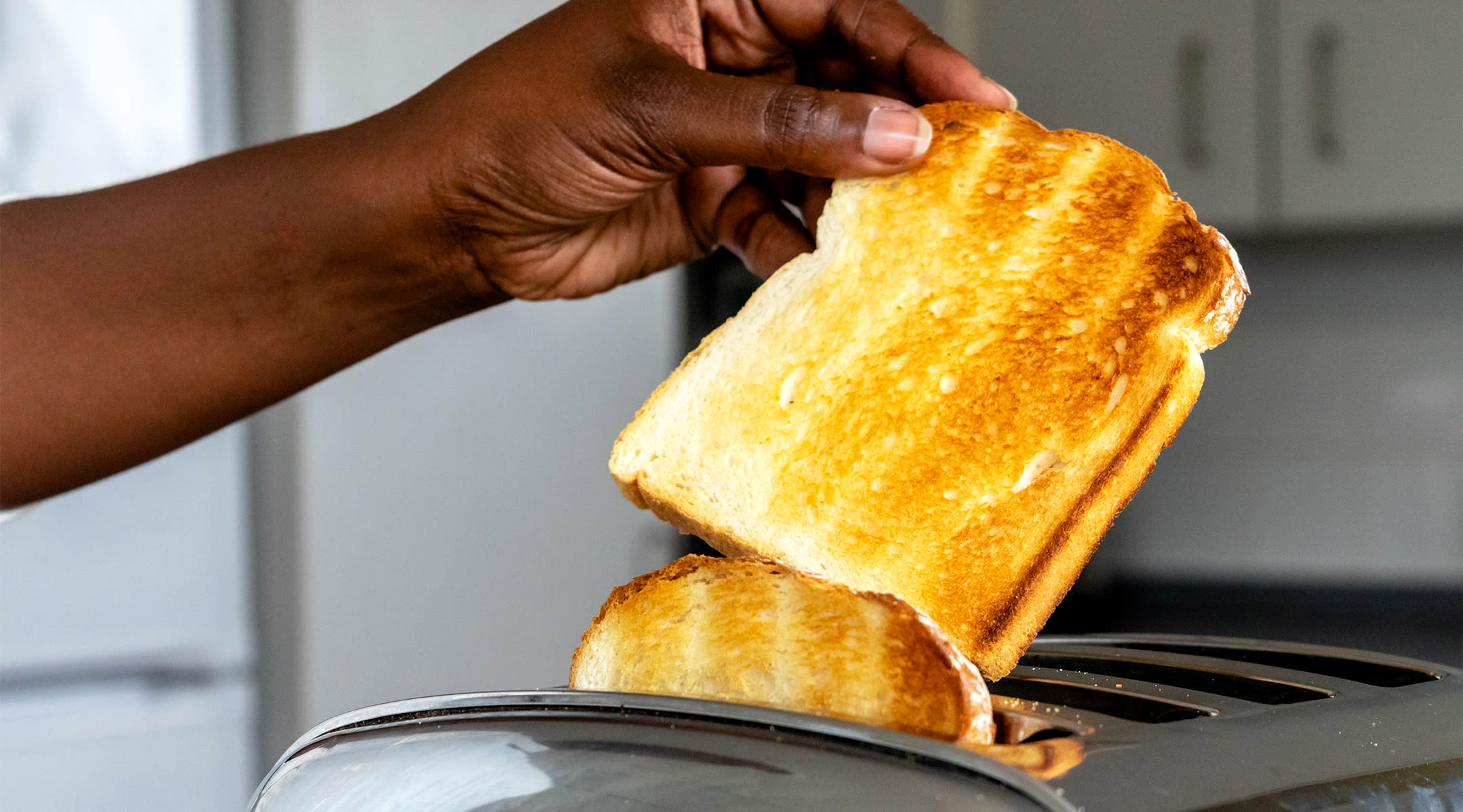 someone taking toast out of toaster