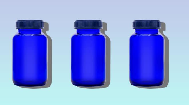 Glass medicine bottles on gradient background.