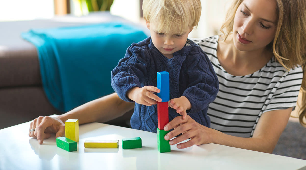 Mom playing blocks with her son.