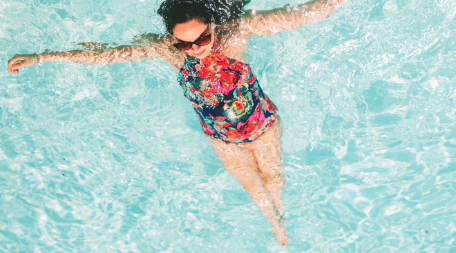 pregnant woman wearing one piece swimsuit and floating in the pool