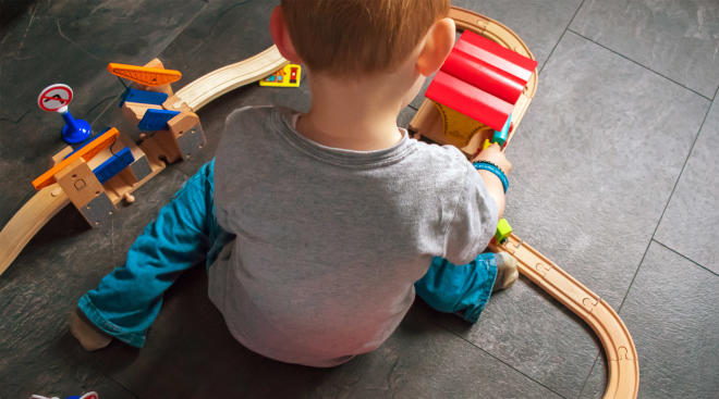 little boy playing with train set
