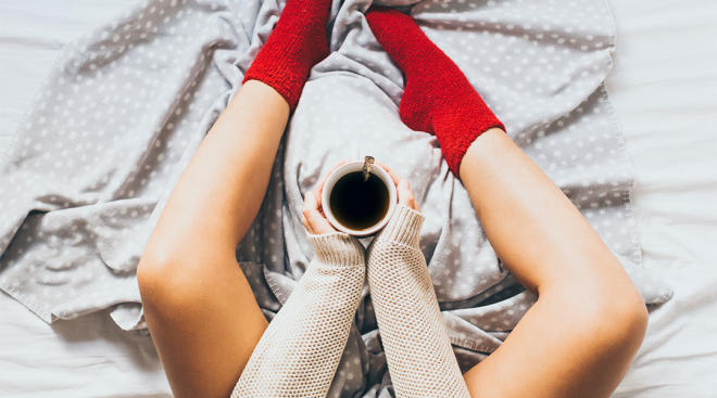 woman wearing red socks and resting her legs in bed