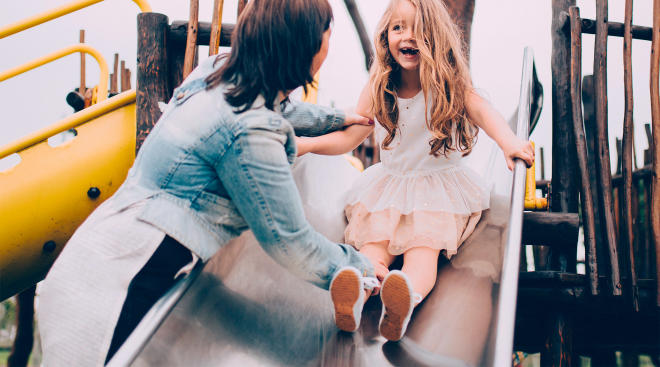 mom on playground with daughter demonstrating helicopter parenting