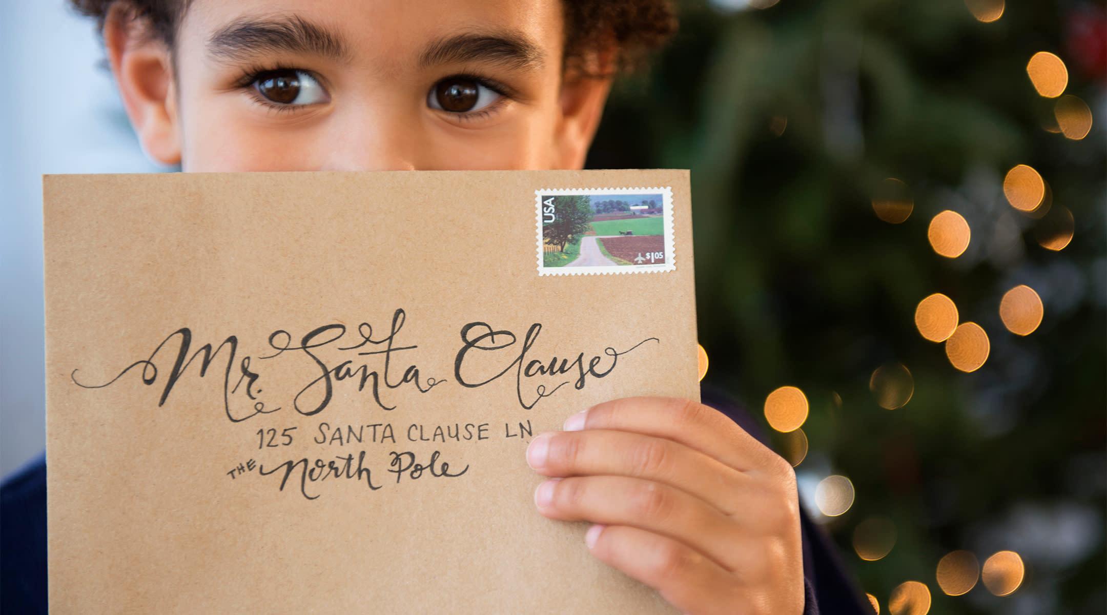 toddler holds envelope addressed to santa