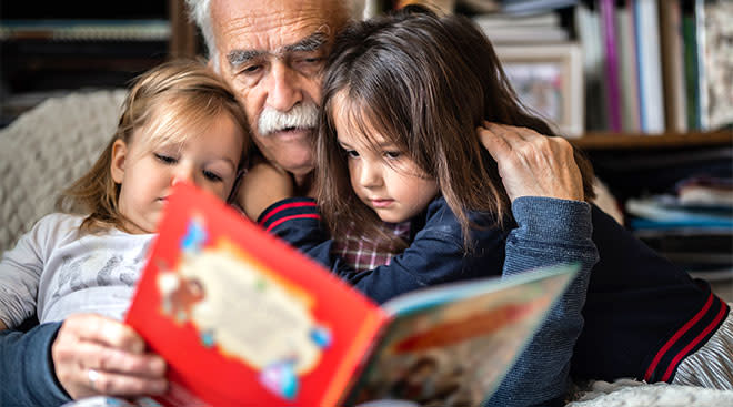 Grandfather sitting with his two grand daughters and reading a book.