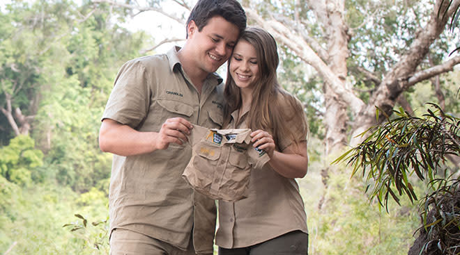 Pregnant Bindi Irwin and her husband Chandler hold up baby safari style onesie.