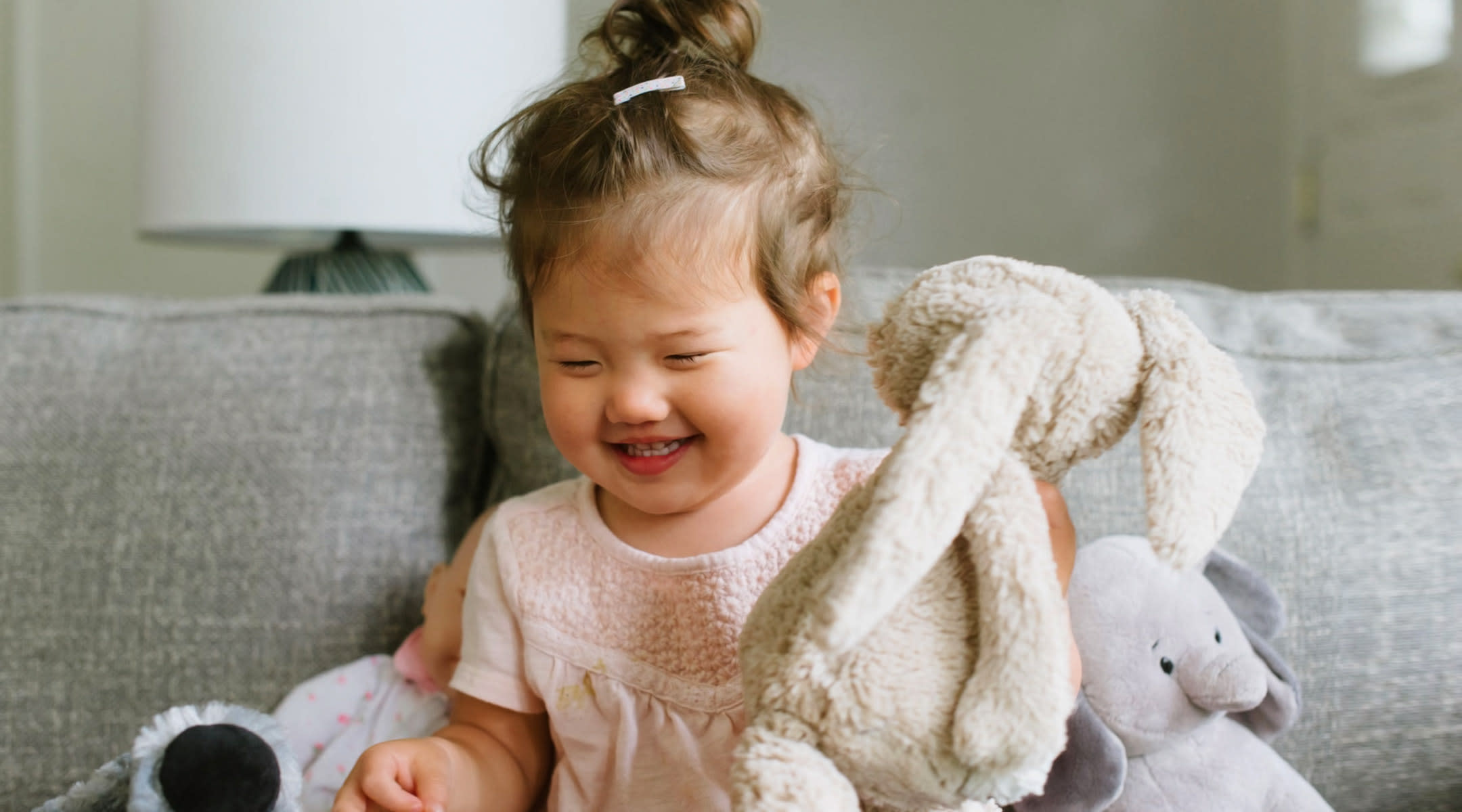happy toddler playing with stuffed animal bunny
