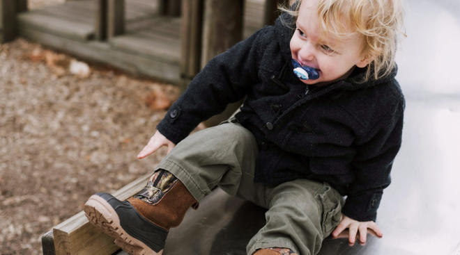 toddler going down slide on playground outdoors