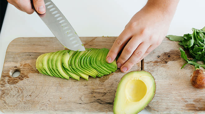 Hands slicing up avocado for baby food for baby led weaning.