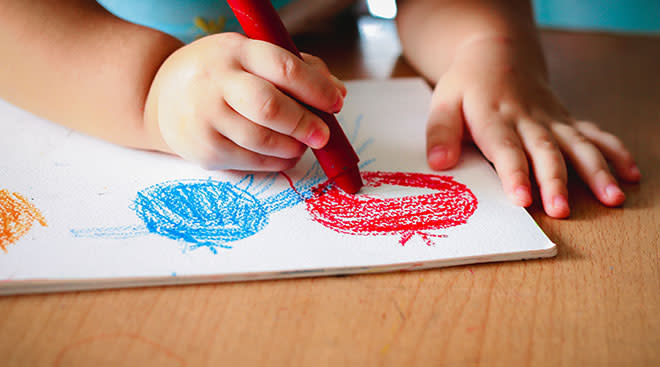 child coloring with crayons on paper