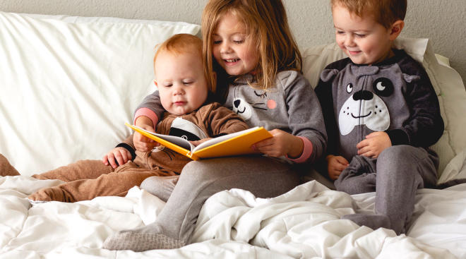 little siblings reading a book together in bed