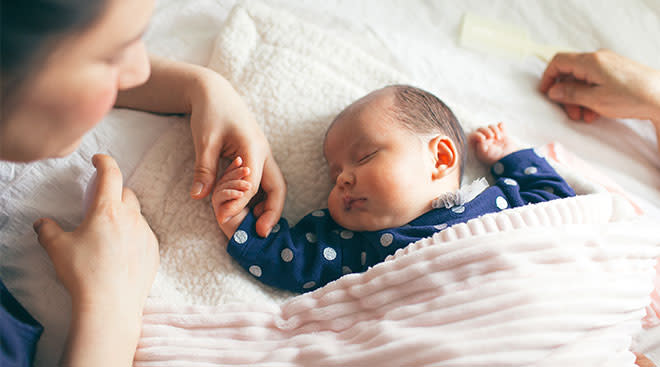 Peaceful new baby sleeping with mom holding its hands.