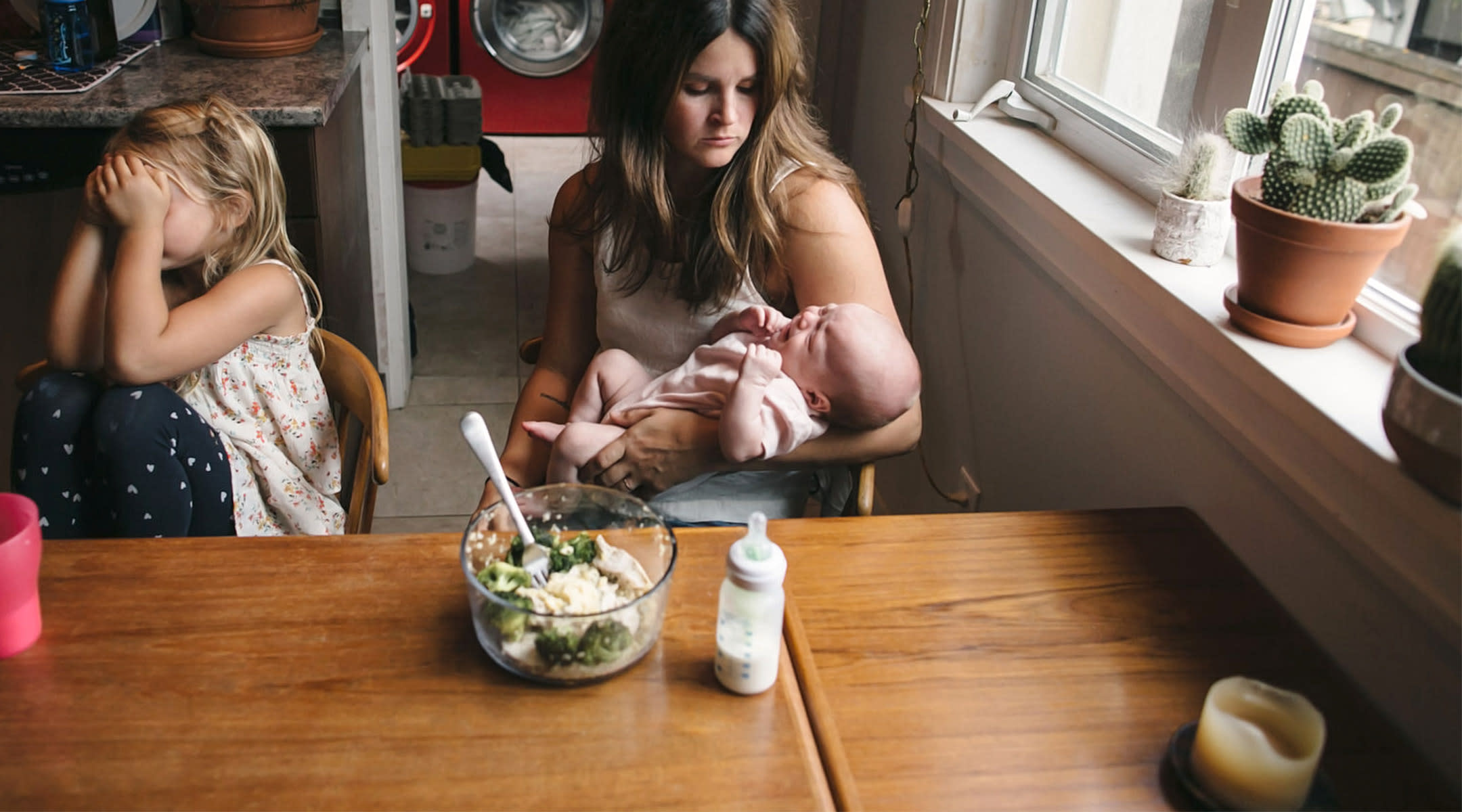 stressed mom with crying baby and child in her kitchen