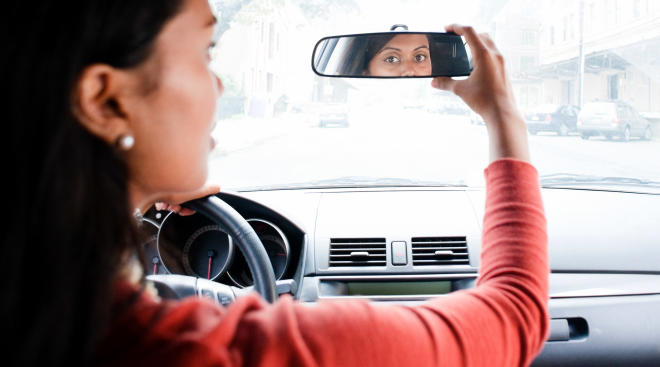 mom in car looking at rearview mirror