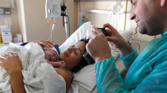 new mom in hospital with dad taking photos