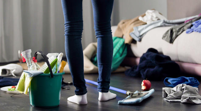 woman stands in the middle of a messy room