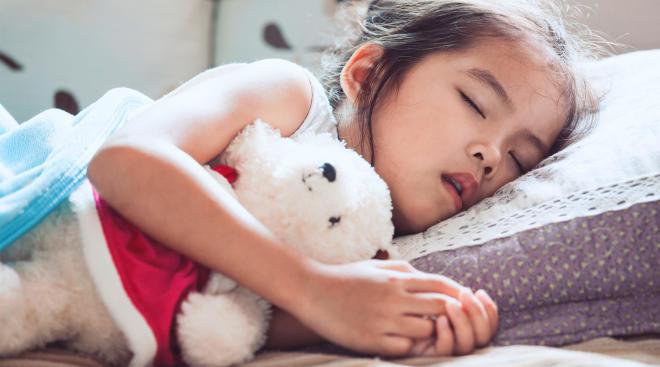 girl napping with stuffed animal