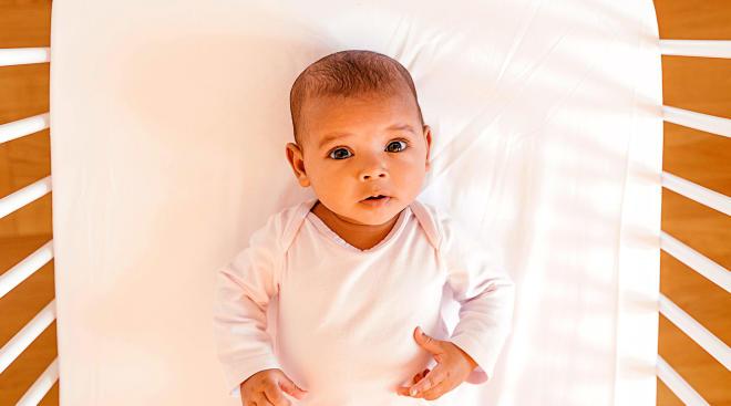 baby in crib looking at camera