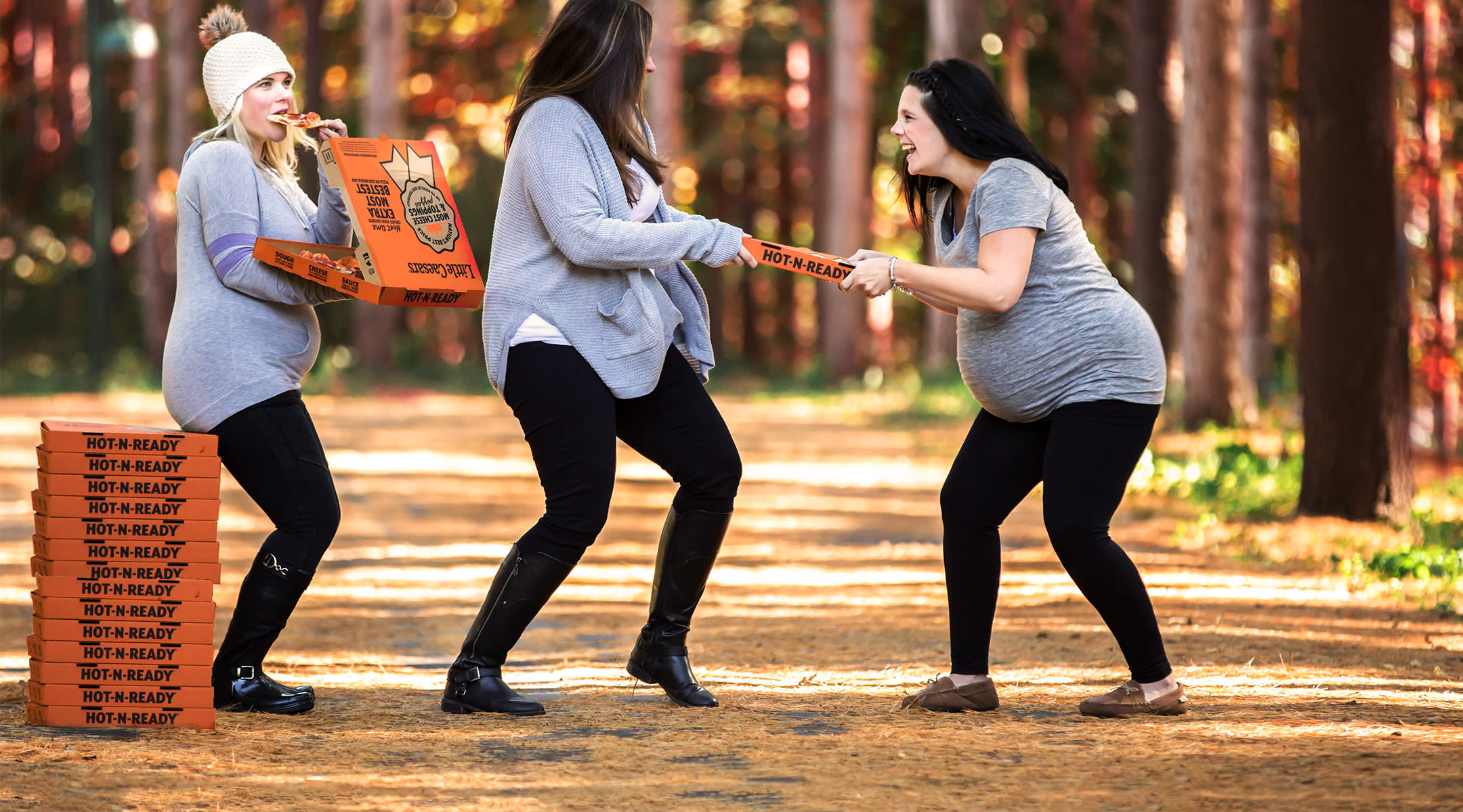 funny photo shoot of pregnant women enjoying and fighting over pizza
