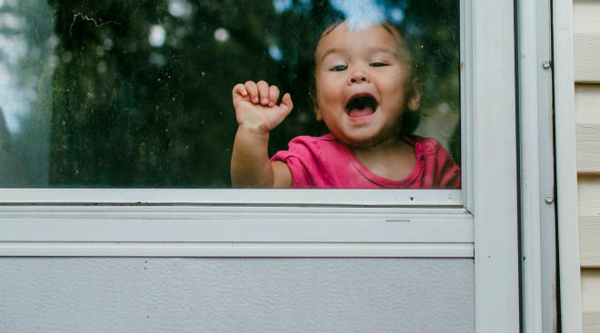toddler girl knocking behind glass back door