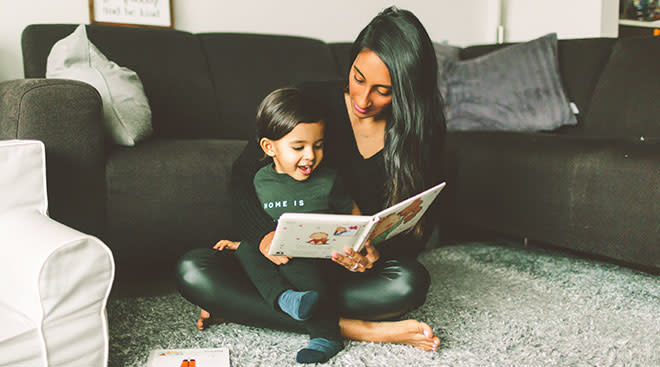 Mom reading a book to her toddler child on the floor at home.