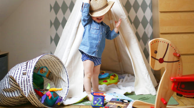 toddler playing in his room with toys and teepee