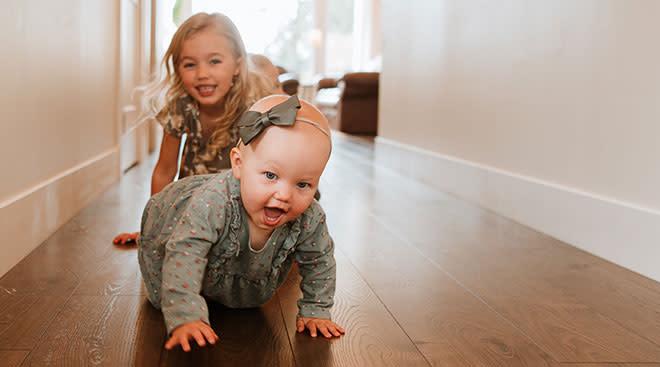 Big sister crawling behind baby sister down hallway at home.